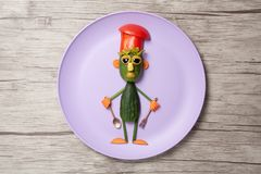 Chief made of cucumbers on purple plate. Cook made with cucumbers, salad, tomato, pepper, carrot, olive and corn. Holding spoon and fork as kitchen attributes royalty free stock photography