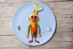 Chief made of vegetables and spoons on plate. Cook made of pepper, cucumber, carrot, radish, pea, and olive. Holds metal kitchen spoons. Wooden background. Canon Stock Images