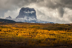 Chief Mountain in Autumn in Glacier National Park, Montana, USA. Chief Mountain in Autumn with layers of aspen trees with fall colors in Glacier National Park royalty free stock image