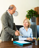 Chief paying to happy assistant an yearly bonus. In office royalty free stock images