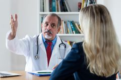 Chief physician explaining medical treatment to female patient. At hospital stock image