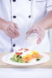 Chief puting salad dressing Stock Images
