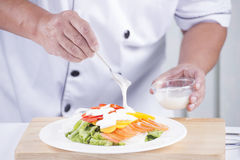 Chief puting salad dressing. / Making Salad concept royalty free stock image