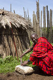 Chief sharpening knife in krall in Maasi Village, Ngorongoro Con Royalty Free Stock Photo
