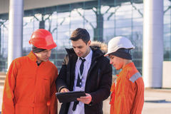 Chief showing the tablet to workers Royalty Free Stock Images