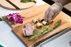 Chief styling the food appetizers on wooden tray on even catering service. royalty free stock photography