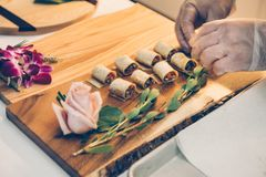 Chief styling the food appetizers on wooden tray on even catering service. royalty free stock photos