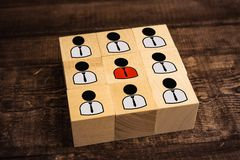 chief and subordinate abstraction figurines on wooden cubes stock photos