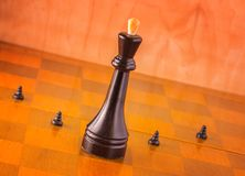 Chief and subordinates. Main and subordinates on a chessboard, pawns fight for the king by sacrificing themselves Royalty Free Stock Images