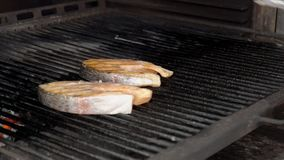 The chief turns over the red fish steak which is being grilled ,by the tongs in his hand. The two pieces of salmon are being cooked on the black barbecue with stock footage