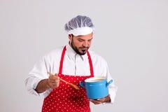 Chiefcook品尝与他的匙子的食物 免版税库存图片