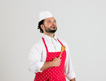 Chief-cook is Holding Spoon on His Heart. Devoted Chief-cook in Red Apron is Holding Wooden Spoon on His Chest Isolated on White Background Stock Photography