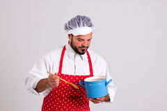 Chief cook is Tasting Food with His Spoon. Chief cook in Red Apron is Looking to Stockpot Isolated on White Background Royalty Free Stock Images