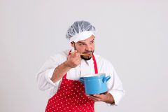 Chief cook is Tasting Soup with His Spoon. Chief cook in Red Apron is Tasting Soup from Stockpot Isolated on White Background Royalty Free Stock Photography