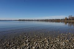 View over Chiemsee with Seebruck in the backgrund. Chiemsee, autumn day, low water, south bavaria, beautiful day stock photography