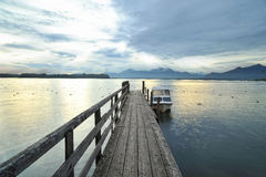 Chiemsee lake at sunries. Boat on the dock Royalty Free Stock Photo