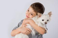 Chien blanc de chiwawa de petit garçon sur le fond blanc Amitié d'animal familier d'enfants Photo stock