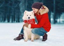 Chien blanc de soin heureux de Samoyed d'embrassement de jeune femme en hiver photos libres de droits