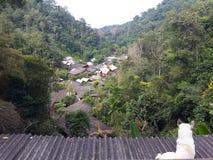 Chien blanc se reposant sur le toit et le visionnement confortable le village de campagne parmi les montagnes, Mae Kampong, Chian Photos libres de droits