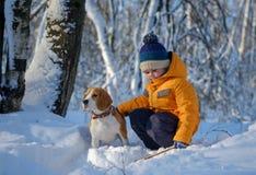 Chien de garçon et de briquet dans la forêt neigeuse d'hiver Photo stock