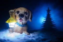 Chien de jouet - un symbole de la nouvelle année sous la neige dans la perspective du sapin s'embranche Le chien de jouet comme s Photo stock