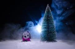 Chien de jouet - un symbole de la nouvelle année sous la neige dans la perspective du sapin s'embranche Le chien de jouet comme s Image libre de droits