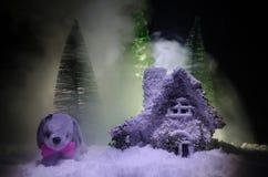 Chien de jouet - un symbole de la nouvelle année sous la neige dans la perspective du sapin s'embranche Le chien de jouet comme s Photo libre de droits