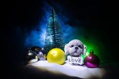 Chien de jouet - un symbole de la nouvelle année sous la neige dans la perspective du sapin s'embranche Le chien de jouet comme s Photos stock