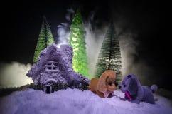 Chien de jouet - un symbole de la nouvelle année sous la neige dans la perspective du sapin s'embranche Le chien de jouet comme s Photographie stock libre de droits