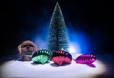 Chien de jouet - un symbole de la nouvelle année sous la neige dans la perspective du sapin s'embranche Le chien de jouet comme s Photographie stock