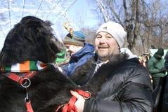 Chien de chien-loup irlandais et son propriétaire à la célébration de jour du ` s de St Patrick à Moscou Photo libre de droits