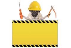 Chien de roquet tenant les pinces et le tournevis derrière le panneau d'avertissement jaune photo stock