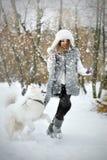 Chien de traîneau blanc avec la fille courant dans la neige photos stock