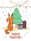 Chien drôle avec les klaxons de cerfs communs, l'arbre de Noël et les cadeaux Photo stock