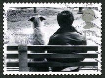 Chien et homme s'asseyant sur le banc Images stock
