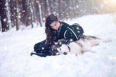 Chien mignon d'embrassement de fille de conte de fées en parc d'hiver Images stock
