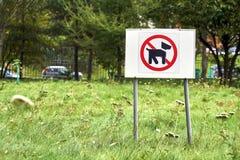 Chiens menaçants de panneau d'avertissement marchant sur la pelouse Image stock