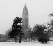 Chiesa alta di Art Deco che si eleva sopra gli alberi nella neve - in bianco e nero Fotografia Stock