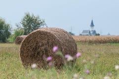 Chiesa, balla di fieno e un campo di grano Immagini Stock