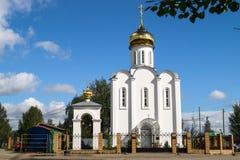 Chiesa bianca elegante graziosa sui precedenti di cielo blu luminoso Immagini Stock Libere da Diritti