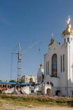 Chiesa bianca ortodossa cristiana della costruzione con le cupole e gli incroci dell'oro dalla gru di costruzione Immagini Stock Libere da Diritti