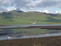 Chiesa bianca rossa sola nel vik in colline dell'erba verde dell'Islanda fotografia stock libera da diritti