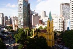 Chiesa cattolica gialla circondata dal vecchio affare e dagli edifici residenziali Fotografie Stock Libere da Diritti