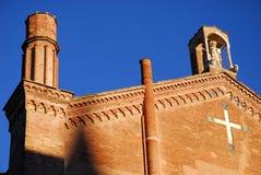 Chiesa con una statua e un incrocio bianco sulla parete a Bologna in Emilia Romagna (Italia) Immagine Stock