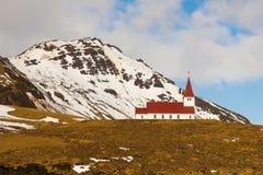 Chiesa cristiana rossa sull'alta collina con innevato Fotografie Stock