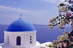 Chiesa a cupola blu di Santorini con i fiori Immagini Stock Libere da Diritti