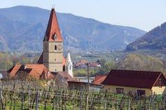 Chiesa del presupposto di vergine Maria in città di Weissenkirchen nel der Wachau con le vigne nella priorità alta l'austria Immagini Stock