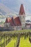 Chiesa del presupposto di vergine Maria in villaggio Weissenkirchen--der-Wachau con nelle vigne nella priorità alta Abbassi Aus Fotografie Stock