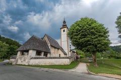 Chiesa dello SV San Giovanni Battista dal lago Bohinj, Slovenia Immagini Stock