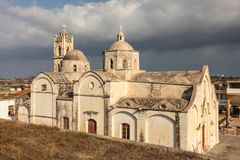Chiesa di Ayios Synesios in Rizokarpaso Dipkarpaz, acceso dal sole di pomeriggio, alcune nuvole pesanti nel fondo Questa città no immagini stock